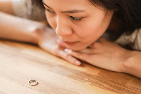 Woman looking at wedding ring thinking about husbands infidelity