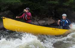 Couple canoeing down rapids