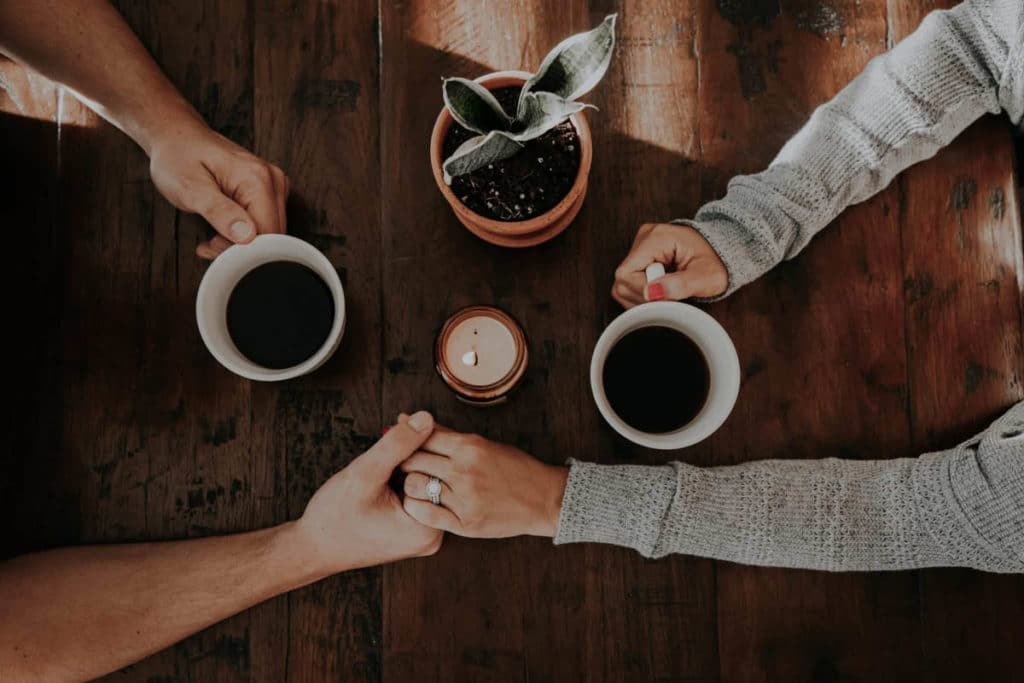 Spouses, husband and wife, holding hands while drinking coffee