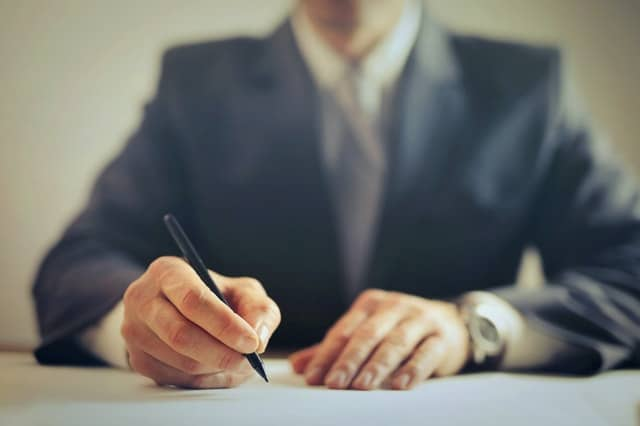 man signing an updated Will