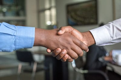 Couple shaking hands over a cohabitation contract