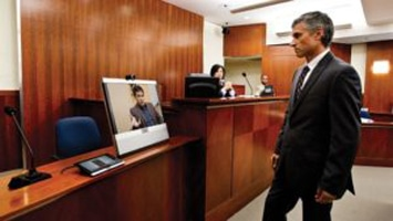 Lawyer having video conference in courtroom